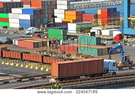 Cargo container, pipe, lumber and train in port poster
