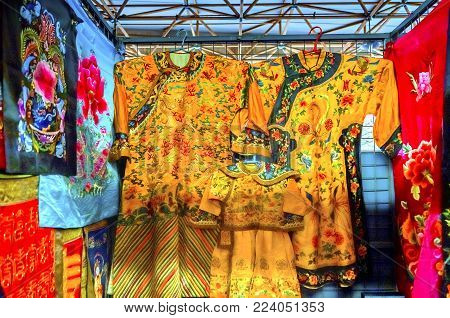 BEIJING, CHINA - NOVEMBER 13, 2017 Blue Red Yellow Chinese Flowers Designs Replica Silk Garments Robes Panjuan Flea Market  Decorations Beijing China.  Panjuan Flea Curio market has many fakes, replicas and copies of older Chinese products, many ancient.