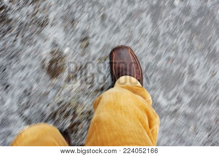 Male legs of asphalt road covered with slippy ice, natural motion