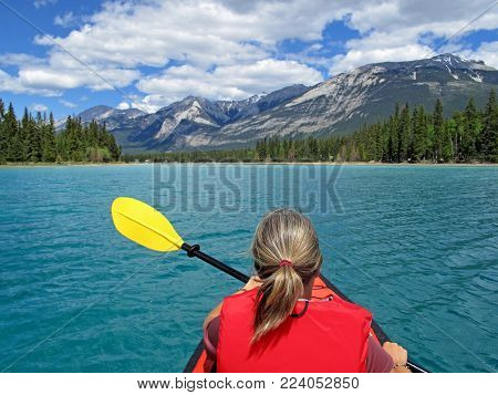 Woman kayaking with red inflatable kayak on turquoise colored Edith Lake, Jasper, Rocky Mountains, Canada