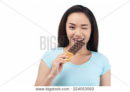 Waist-up portrait of cheerful Asian woman giving wink while standing against white background and biting chocolate bar