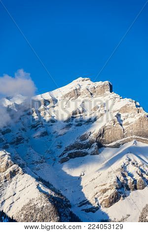 Focus on the summit of Cascade Mountain in the Bow River Valley of Banff National Park. At 9,836 feet, it is the highest mountain in the town of Banff and popular among hikers and mountain climbers. Vertical orientation.