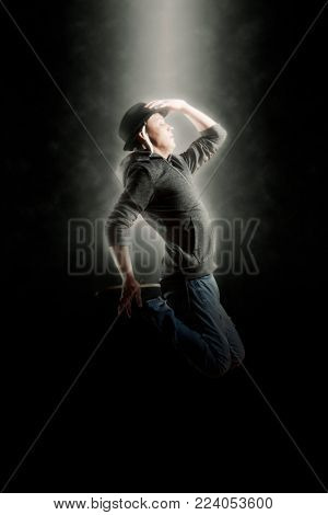 Young man break dancing on smoke background. Soft focus