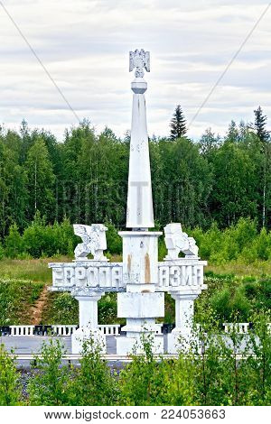 PERM KRAI, RUSSIA - JULY 18, 2014: Stella-divide Europe-Asia in the Perm region against the background of trees and sky. Russia, Urals. Translation: Europe-Asia
