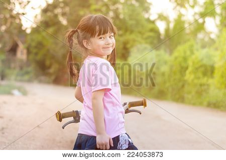Happy little asian girl smiling with her bicycle selective focus.