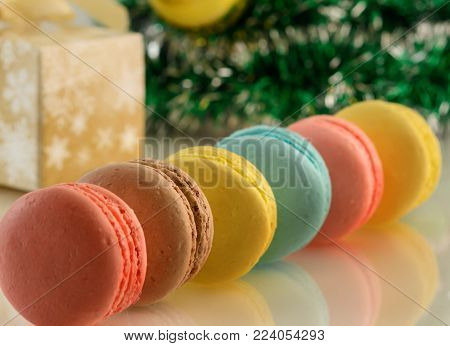 Tasty color macaroos and a cristmas tree on white table