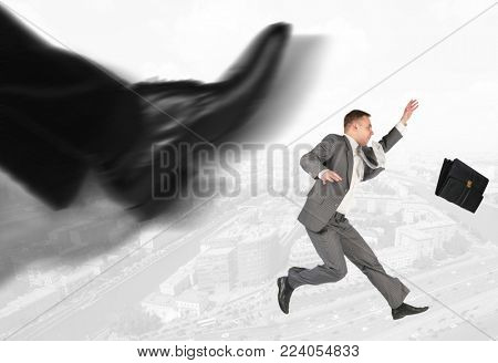 Collage with falling businessman with briefcase on background of city panorama and bosss leg, firing