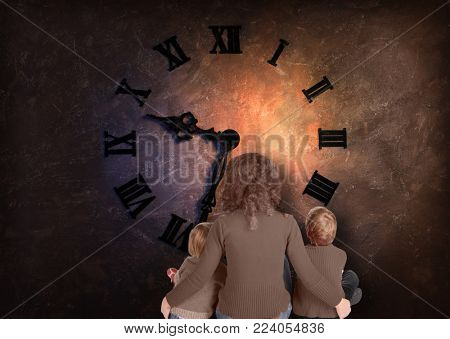 Mother with her son and daughter are sitting opposite wall with big clock with Roman dial, view from back