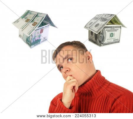 Pensive thinking young man in red sweater and two houses of money, dollars and rubles