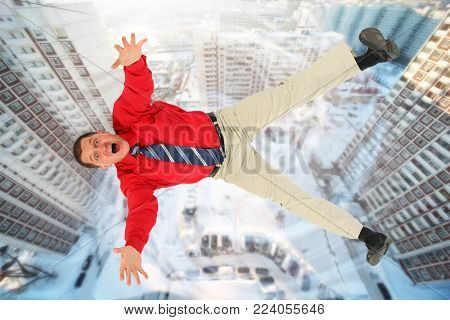 Collage with falling businessman in red shirt against backyard of tall buildings, above view
