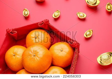 Group of orange tangerine in Chinese pattern tray with gold ingots on red table top. Chinese new year concep.Chinese Language ingot is wealthy poster