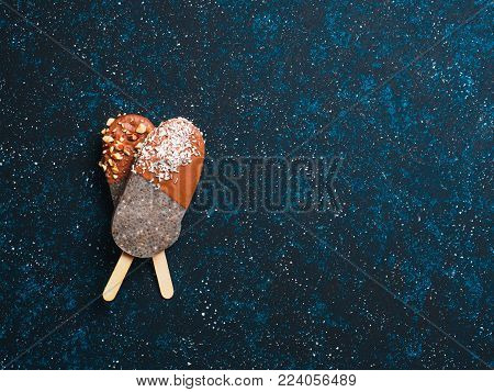 Chia popsicle with chocolate on dark blue background. Healthy recipe and idea homemade vegan popsicle ice cream. Easter dessert idea. Copy space for text. Top view or flat-lay.
