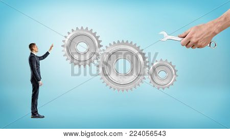 A small businessman points to giant interlocked gears while a big male hand holds a wrench near them. Business and technology. Manufacturing problems. Industry and commerce.