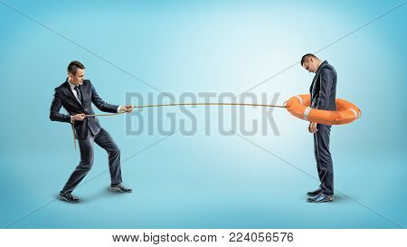 A businessman catches another man with an orange life buoy used as a lasso. Caught by competition. Restricted business. Bound by banking rates.