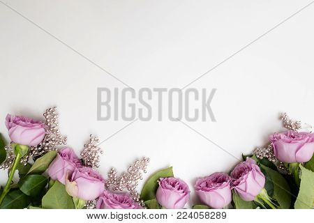 Pink roses flowers on the top of white background with silver beads adornment. Elegant Women's or Mother's Day backdrop
