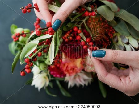 Woman creating autumn flower and berries arrangement on dark background. Bouquet design and composition art ikebana.