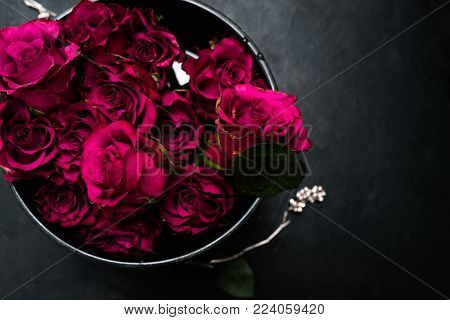 Expression of love and romance. Beautiful bouquet of red roses in a box on dark background. Burgundy flowers to show true feelings