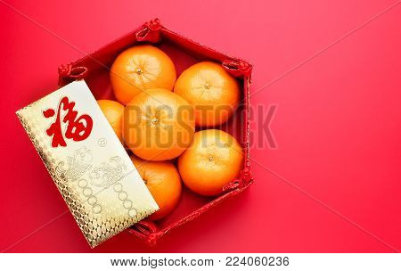 Group of orange tangerine in Chinese pattern tray and envelope packet ang pow on red table top. Chinese new year concep.Chinese Language on envelop is happiness