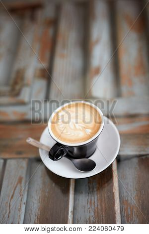 Closeup photo of a cup of delicious cappuccino on wooden surface. View from above.