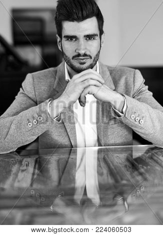 Closeup portrait of confident young businessman sitting at table, elbowing, looking at camera.