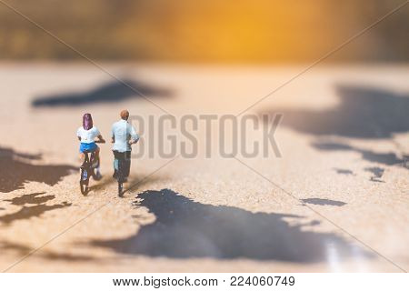 Miniature People Travelers Riding Bicycle On World Map , Traveling And Exploring The World Concept