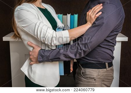 Man touching woman's loin - sexual harassment in business office