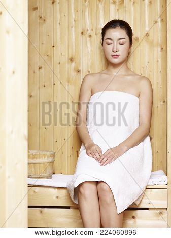 beautiful young asian woman wrapped in white towel sitting in sauna, eyes closed.
