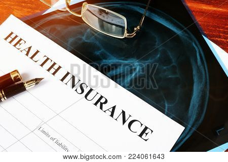 Health insurance policy concept. Claim form and X-ray on a table.