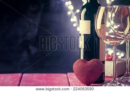 Valentines day background with red wine, wine glass and gift box over shining background