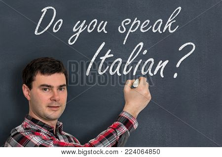 Do you speak Italian? Man with chalk writing on blackboard - learning language concept