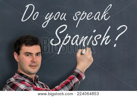 Do you speak Spanish? Man with chalk writing on blackboard - learning language concept