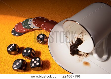 Game over and spill coffee with accessories for casinos. In the picture there is poker chips and dice as a symbol playing to online game.