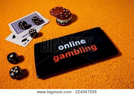 Gambling online with accessories for casinos. In the picture there is a smartphone as a symbol playing to online game.