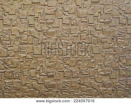 Gold colored wall with 3D geometric shapes background photograph. Golden color wall with raised 3D geometric pattern shapes on it, photograph shot outside in natural light.