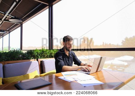 Tired quantity surveyor working at cafe table with diagram and statistic documents. Persistent man dressed in classic black shirt sitting at sofa near green indoor plants. Concept of  preparing estimates and costs of work, keeping track variations to cont