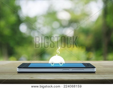 Restaurant cloche flat icon on modern smart phone screen on wooden table over blur green tree in park, Food delivery concept