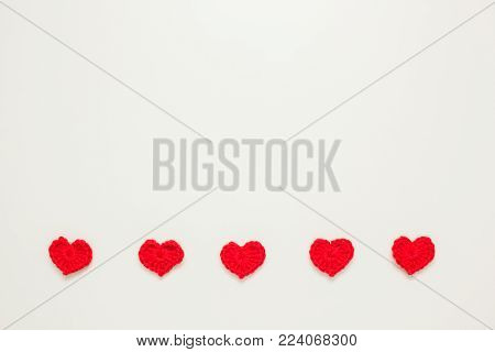 Horizontal row of red knitted hearts on the white bacground