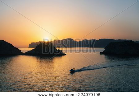 The boat yacht sails near Santa Ponsa coastline at sunset in Morro d'en Pere Joan bay in Mallorca, Balearic islands of Spain. Es Malgrat rocks.