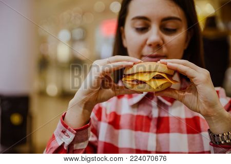 young woman eat cheeseburger hold in hand in fron of face