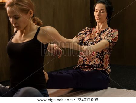 Masseur massaging back of female in spa resort, relaxed patient enjoys. Thai massage or Thai yoga massage treatment