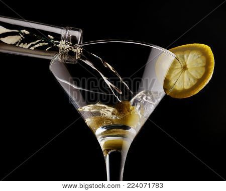 Classical martini in chilled glass over black background, garnished with olive and lemon. Close up.