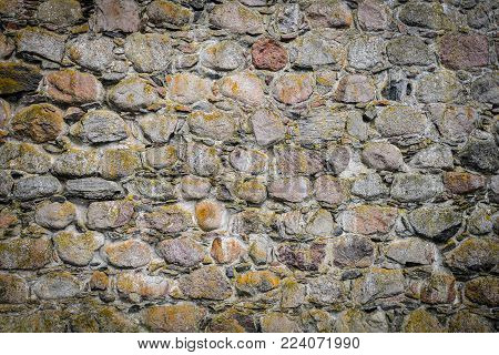 Part of ancient stone wall for background or texture. Beautiful old grey stone wall background with moss and darken edges. Stone wall background for banners, flyers and design