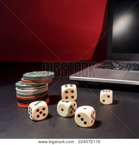 Casino online on the Internet concept. On the table is a laptop and accessories for gambling.