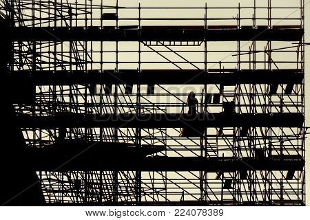 silhouette scaffolding building construction, black profile structure of scaffolding warm orange colors sunset, construction, architecture engineering