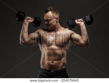 Bodybuilder in black shorts holding dumbell. Studio shoot on grey background