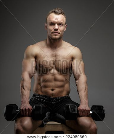 Muscular bodybuilder guy sitting on chair and doing exercises with dumbell on grey background