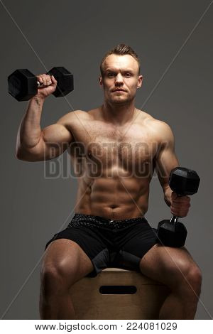 Muscular guy sitting on podium and doing exercises with dumbells. Isolated on grey background