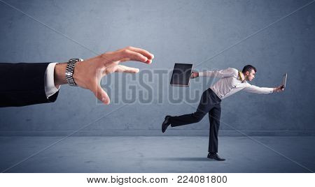 Young miniature businessman running from a big hand with blueish background