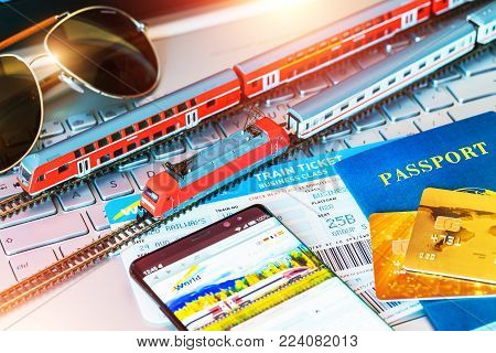 Red toy passenger train, railway travel tickets, passport, bank card and eyeglasses on laptop or notebook computer PC with selective focus effect