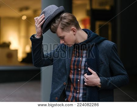 Stylish young man taking off his hat. Fashionist and trend setter. Love for clothing. Haute couture lifestyle